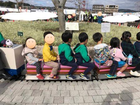 ミニ電車に乗る子供たち